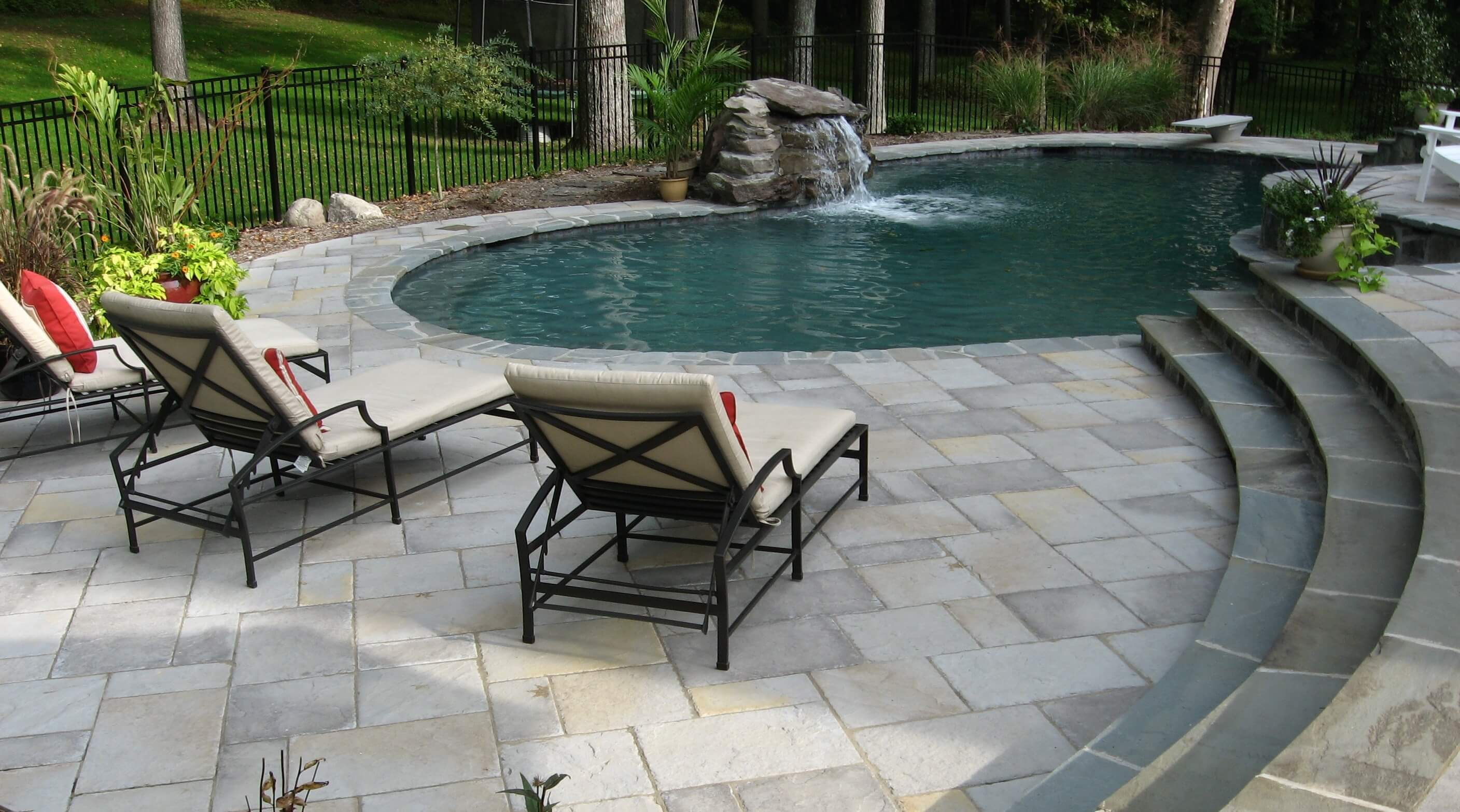 Freeform Pool With Stone Patio & Waterfall